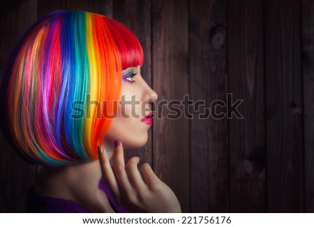beautiful woman wearing colorful wig and showing colorful nails against wooden background - stock photo
