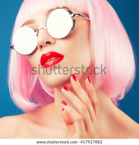 beautiful woman wearing colorful wig and silver sunglasses against blue background - stock photo