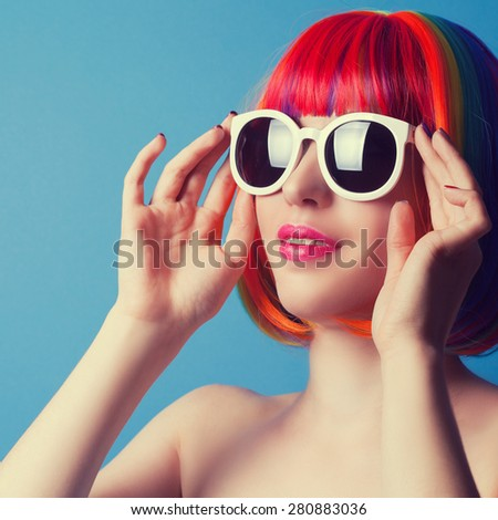 beautiful woman wearing colorful wig and white sunglasses against blue background - stock photo