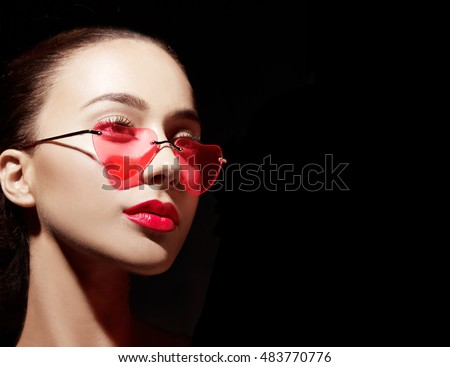 Beautiful woman wearing funny heart shape red sunglasses isolated on black.