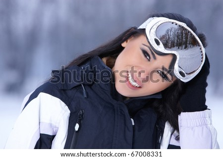 Beautiful woman wearing goggles in snowy winter outdoors - stock photo