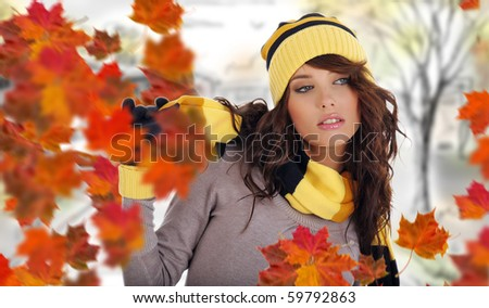 Beautiful woman wearing hat and gloves and maple leaves - stock photo