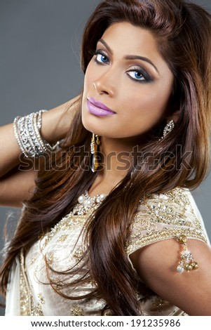beautiful woman wearing indian traditional outfit on  grey background - stock photo