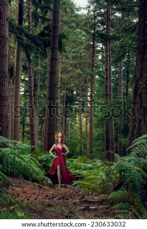 Beautiful woman wearing long red dress  in forest with deers - stock photo
