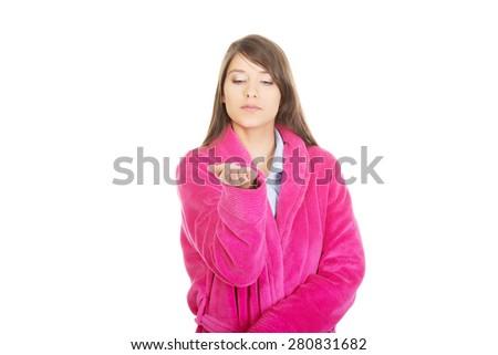 Beautiful woman wearing pink bathrobe showing empty palm. - stock photo