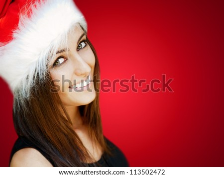 Beautiful woman wearing Santa Claus hat smiling to camera - stock photo