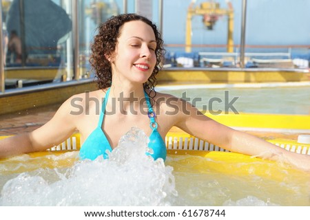 beautiful woman wearing swimming suit is relaxing in hot tub on cruise ship. - stock photo
