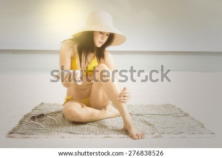 Beautiful woman wearing swimsuit at beach while applying sunscreen on her body, shot with an instagram effect - stock photo