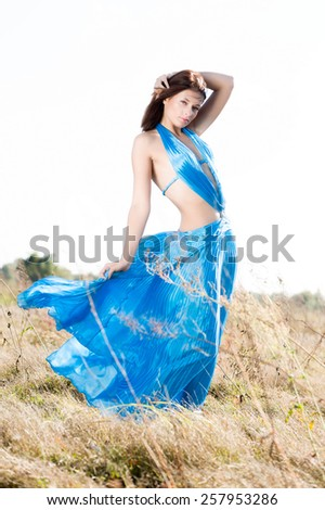 Beautiful woman wearing turquoise long dress standing in a meadow. - stock photo