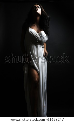 Beautiful woman wearing white dress over a grungy wall - stock photo