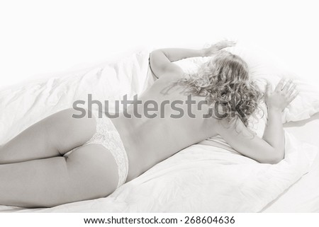 Beautiful woman wearing white panties, she's lying on white bed in front of white studio background, monochrome photo with copy space above the model - stock photo