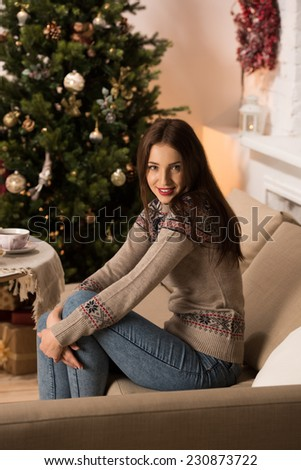 Beautiful woman wearing winter outfit drinking tea with candy at home near Christmas tree - stock photo