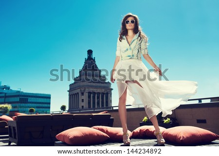 Beautiful woman white loose skirt, high heels, and jeans jacket standing on the bed on the rooftop - stock photo