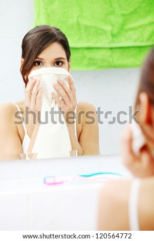 Beautiful woman wipes her face with a towel at bathroom - stock photo