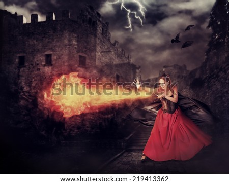beautiful woman witch trains in medieval castle cast magic - fireball - stock photo