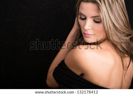 Beautiful woman with a backless dress - isolated over a black background - stock photo
