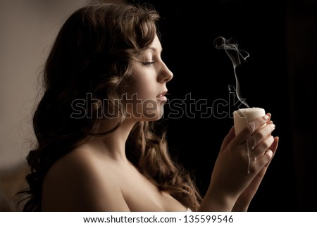 Beautiful woman with a candle on a black background - stock photo