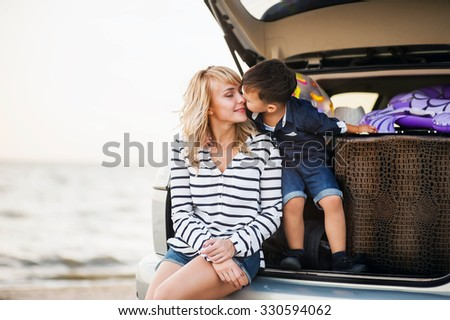 Beautiful woman with a child of four years in the car are going to have a trip - stock photo