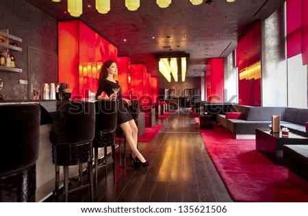 beautiful woman with a cocktail in a luxury lounge - stock photo