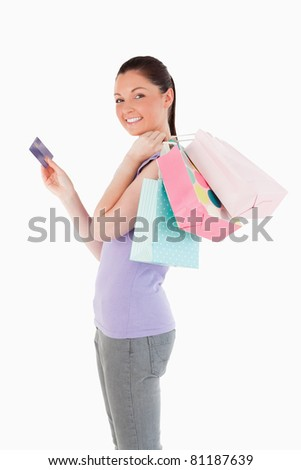 Beautiful woman with a credit card holding shopping bags while standing against a white background