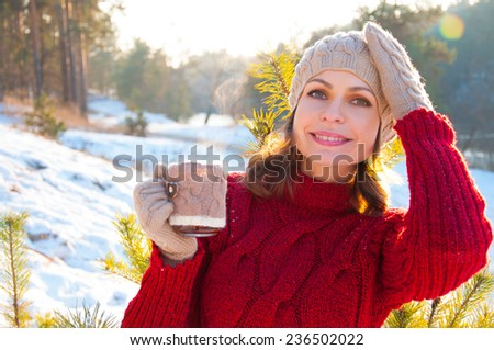 Beautiful woman with a cup of tea in the winter outdoors