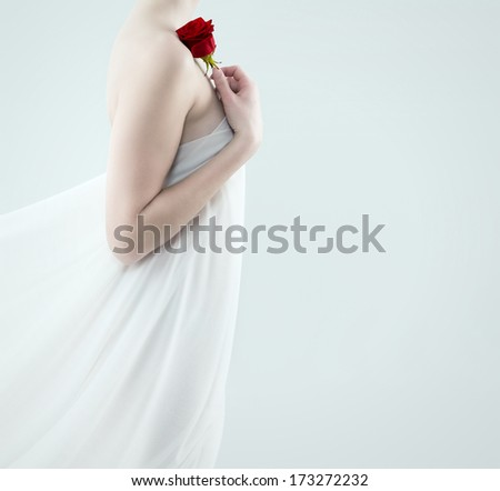 beautiful woman with a fabric drape holding red rose on her shoulder