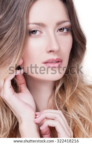 Beautiful woman with a gentle make-up on her face, her hair curly, she looks into the camera. Woman with smooth skin and perfect makeup on her face, her hand near the neck. Beauty. Cosmetology - stock photo