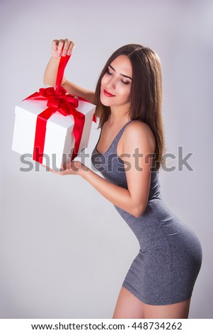 Beautiful woman with a gift box in her hands.