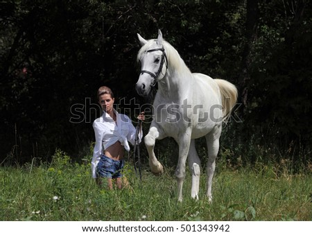 Beautiful woman with a horse having fun at the farm