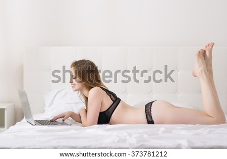Beautiful woman with a laptop on the bed