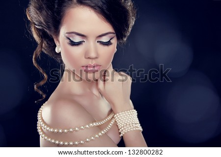 Beautiful woman with a pearl necklace on the bared shoulders - stock photo