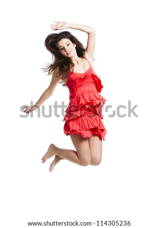 Beautiful woman with a red dress dancing and jumping, isolated on white - stock photo