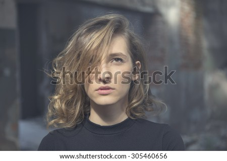 Beautiful woman with a serious expression on her face looking straight ahead with a view of abandoned building in the background - stock photo