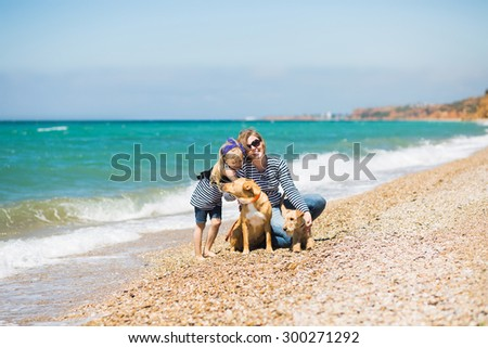 Beautiful woman with adorable daughter and dogs resting on the beach - stock photo