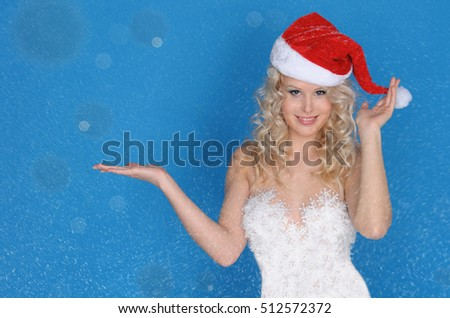 Beautiful woman with an open hand and snow on blue background