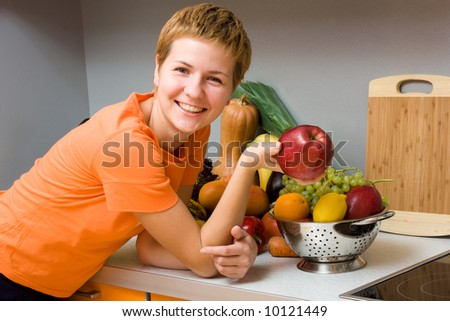 Beautiful woman with apple and fresh fruits in the kitchen - stock photo