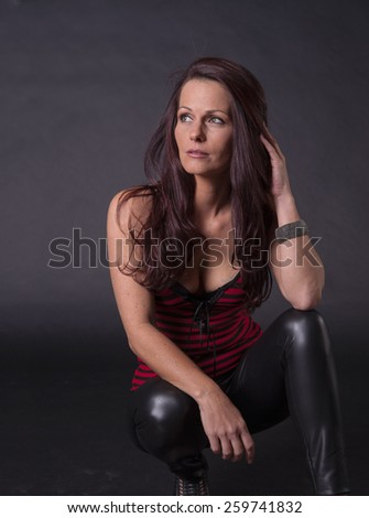 Beautiful woman with arm on her knee - stock photo