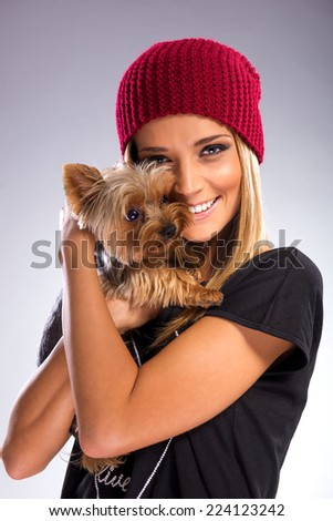 Beautiful woman with autumn fashion, holding yorkshire terrier dog - stock photo