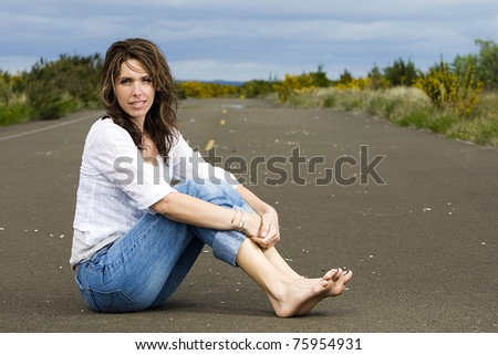 Beautiful Woman with bare feet sitting in the middle of the road. - stock photo