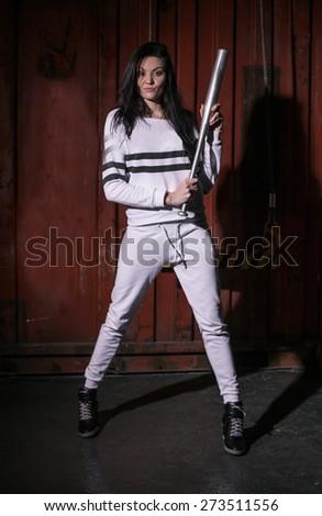 Beautiful woman with baseball bat in studio - stock photo