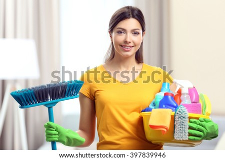 Beautiful woman with basin of cleaning supplies - stock photo