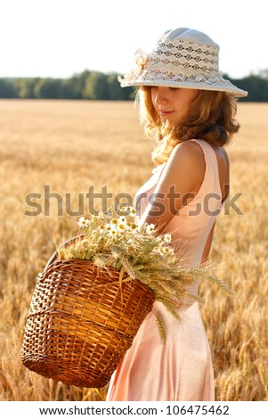 Beautiful woman with basket full of ripe ears wheat and daisies in the wheat field on a sunny day - stock photo