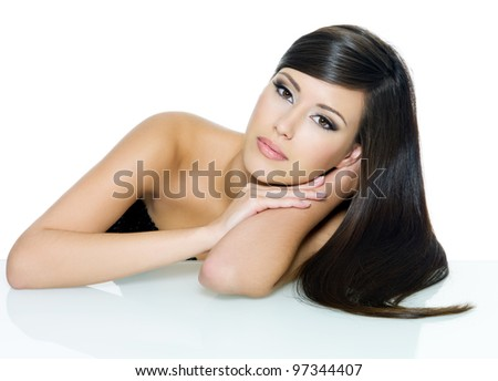 Beautiful woman with beauty long straight  hair posing sitting from the table - on white background - stock photo