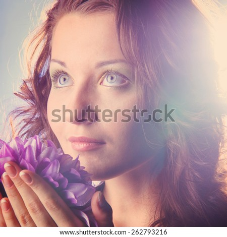 beautiful woman with big flower on blue background - stock photo