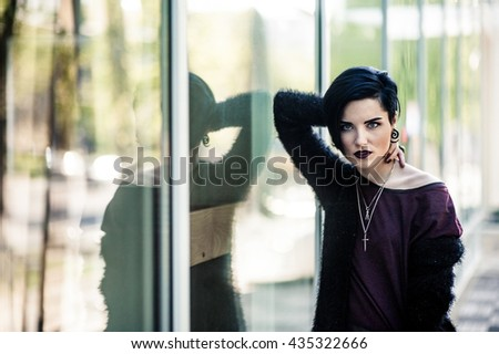 Beautiful woman with black hair and dark lipstick standing near the large windows and looking at the camera