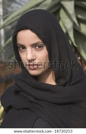 Beautiful woman with black head scarf on - stock photo