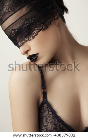 beautiful woman with black lace over her face, studio shot