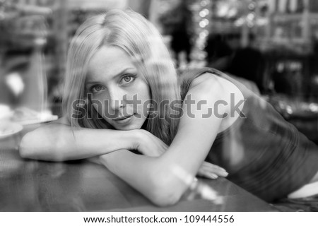 beautiful woman with blond hair near a window. view from outside. black and white - stock photo