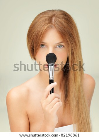 beautiful woman with blusher brush on nose - stock photo