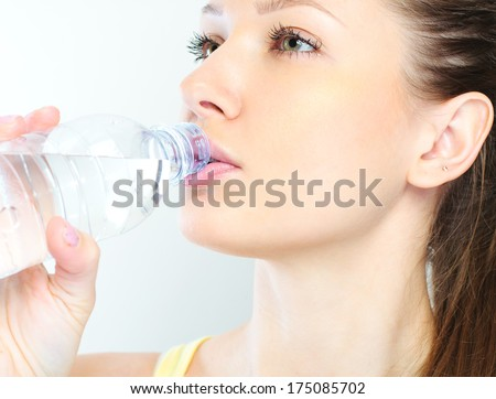 beautiful woman with bottle of water over white - stock photo